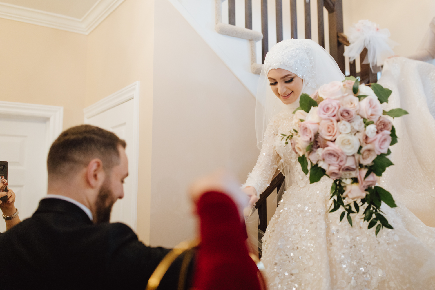 bride coming down the stairs to meet groom